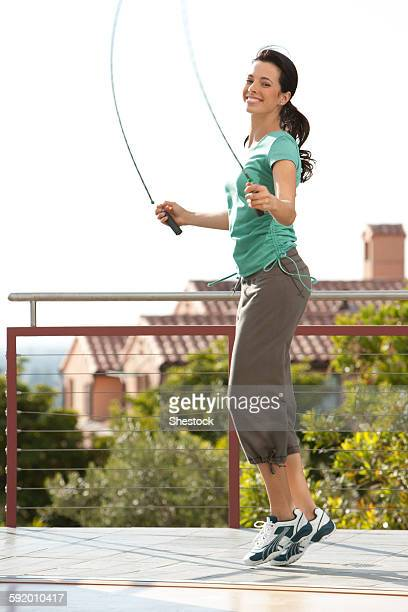 Caucasian woman jumping rope on urban rooftop