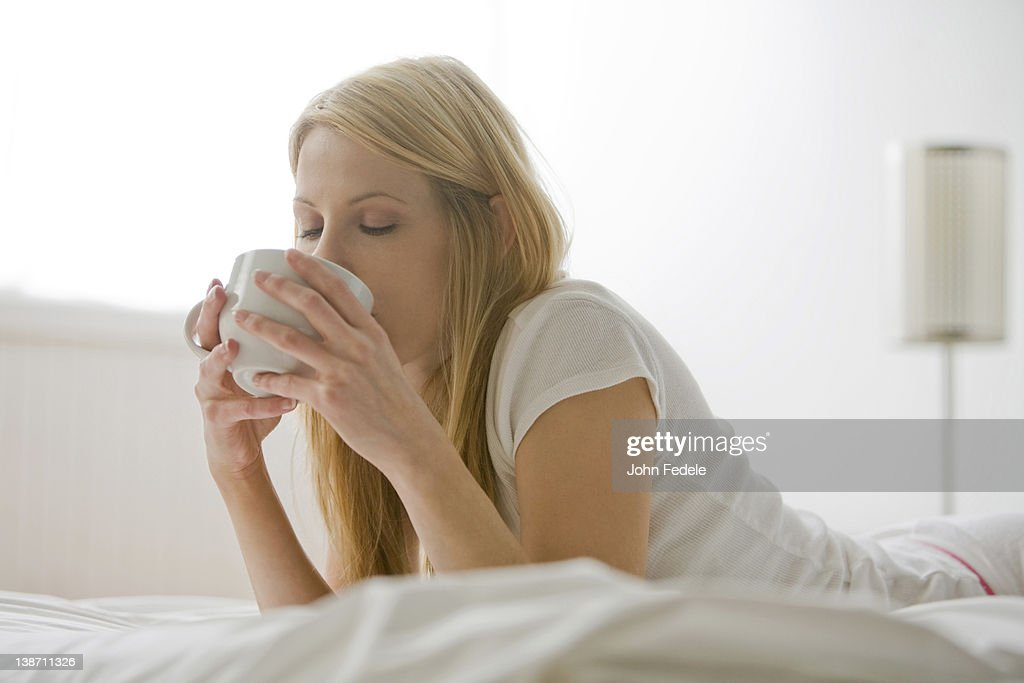 Caucasian woman laying in bed drinking coffee : Stock Photo