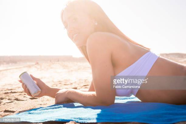 Caucasian woman laying on beach holding can