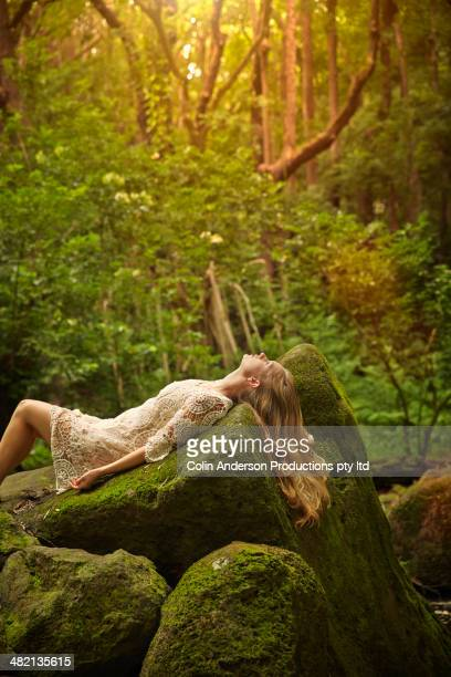 Caucasian woman laying on rock in woods