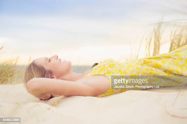 Caucasian woman laying on sand dune