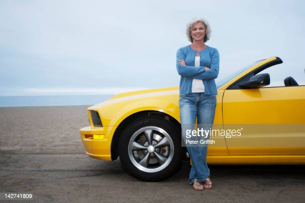 Caucasian woman leaning on convertible at beach