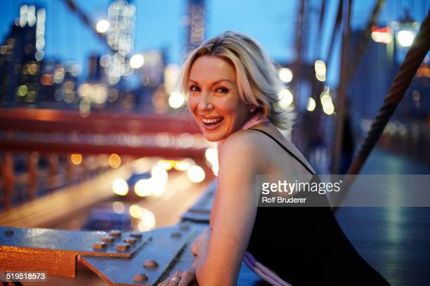 Caucasian woman leaning on railing on Brooklyn Bridge, New York City, New York, United States