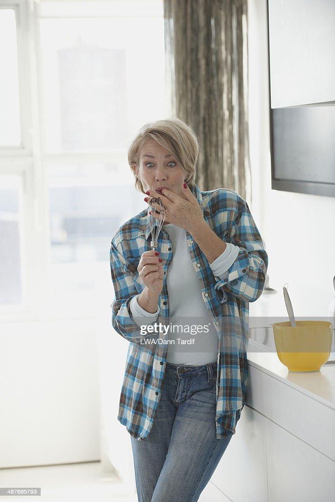 Caucasian woman licking whisk n kitchen : Stock Photo
