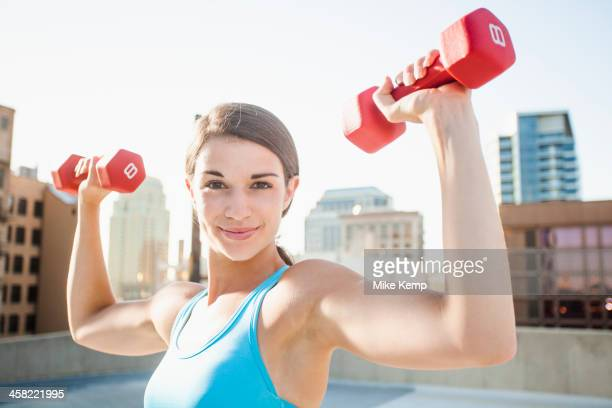 Caucasian woman lifting dumbbells on urban rooftop