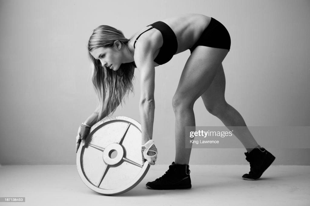 Caucasian woman lifting weight disc