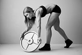 Caucasian woman lifting weight disc