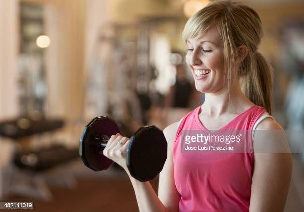 Caucasian woman lifting weights in gym