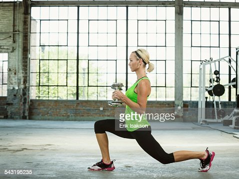 Caucasian woman lifting weights in warehouse gym