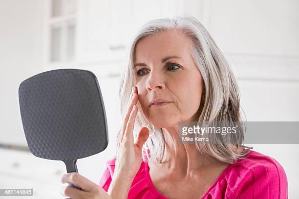 Caucasian woman looking at skin in mirror