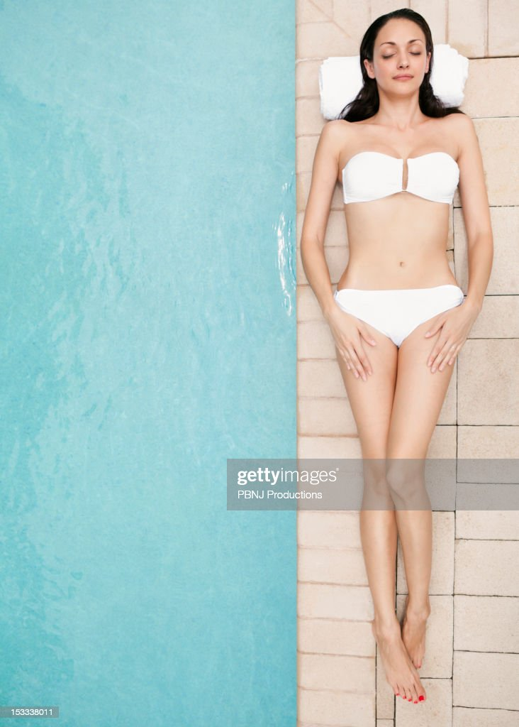 Caucasian woman lying at poolside