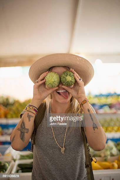 Caucasian woman making a face with fruit in farmers market