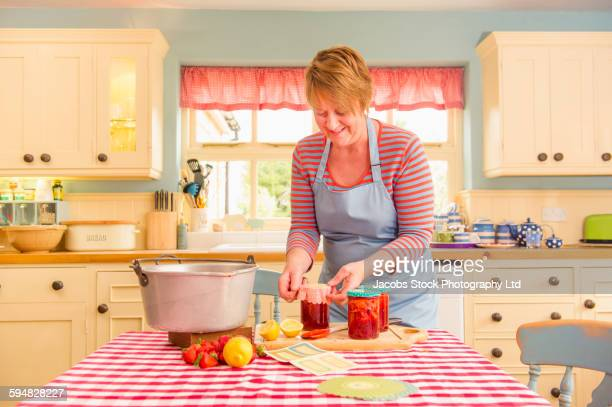 Caucasian woman making jam in kitchen