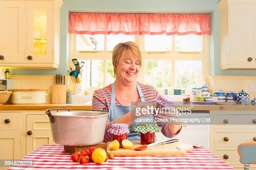 Caucasian woman making jam in kitchen