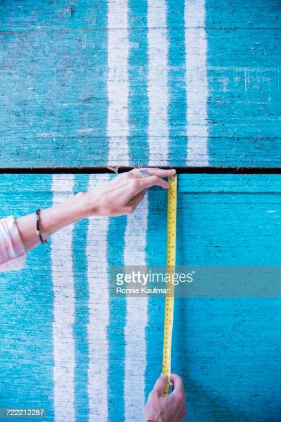 Caucasian woman measuring blue wooden boards
