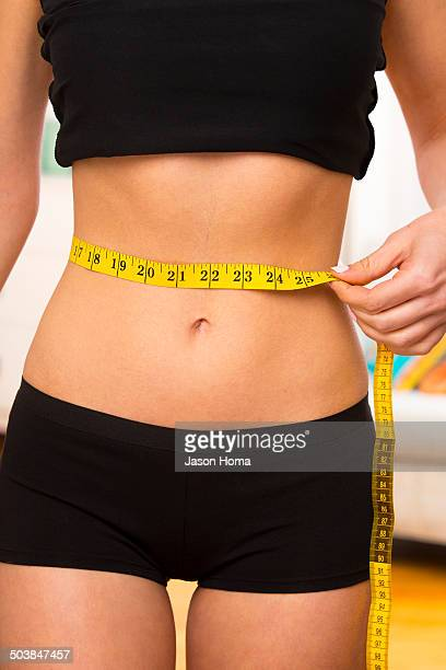 Caucasian woman measuring her waist