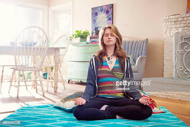 Caucasian woman meditating in living room