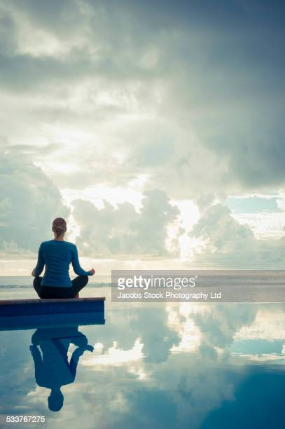 Caucasian woman meditating near swimming pool