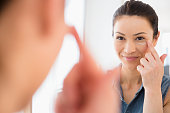 Caucasian woman moisturizing her face