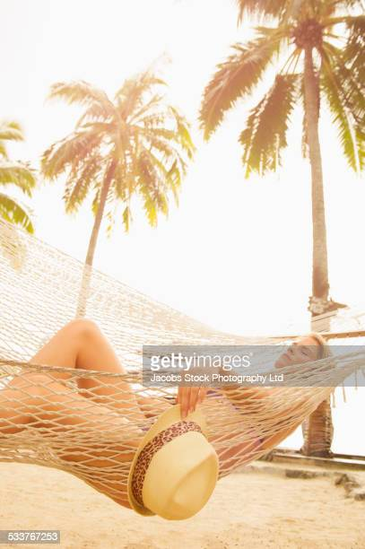 Caucasian woman napping in hammock