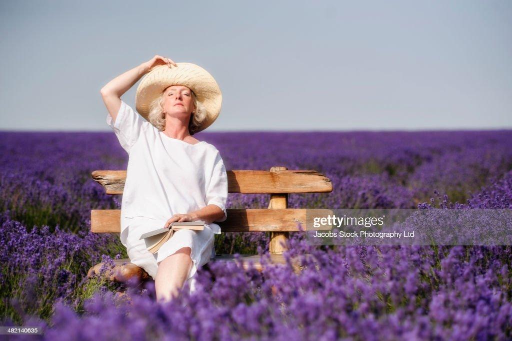 Caucasian woman on bench in lavender field
