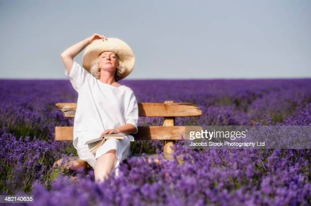 Caucasian woman on bench in lavender field