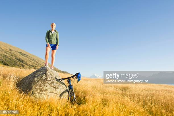 Caucasian woman on boulder in rural landscape