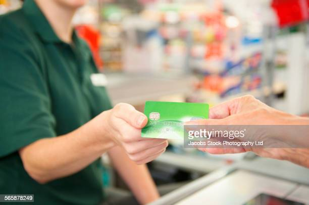 Caucasian woman paying cashier at grocery store checkout