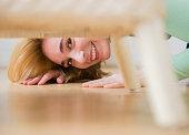 Caucasian woman peeking under chair