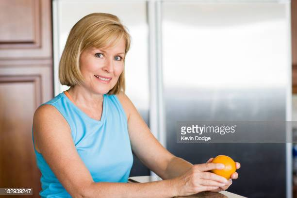 Caucasian woman peeling fruit in kitchen