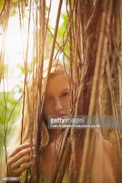 Caucasian woman peering through banyan tree vines