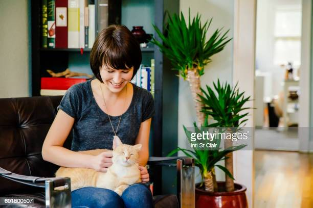 Caucasian woman petting cat in living room