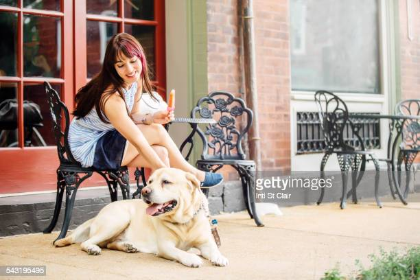 Caucasian woman petting dog at sidewalk cafe