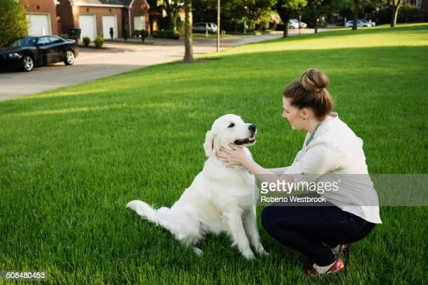 Caucasian woman petting dog in park