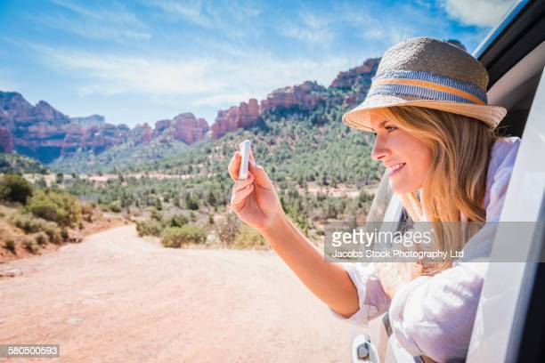 Caucasian woman photographing desert landscape, Sedona, Arizona, United States