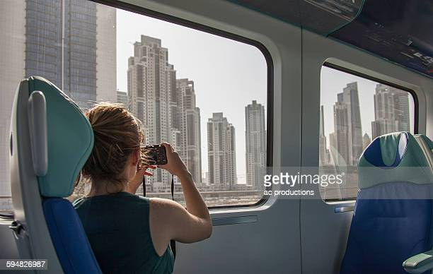 Caucasian woman photographing Dubai cityscape on train, Dubai Emirate, United Arab Emirates