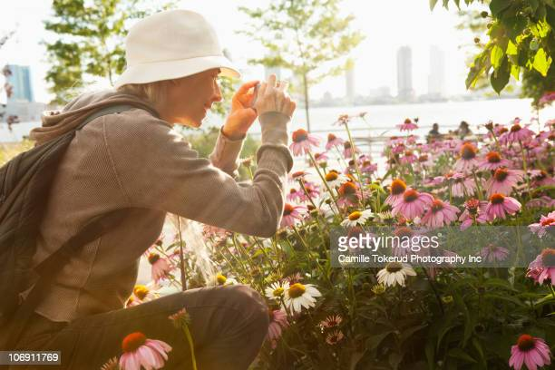 Caucasian woman photographing flowers with digital camera