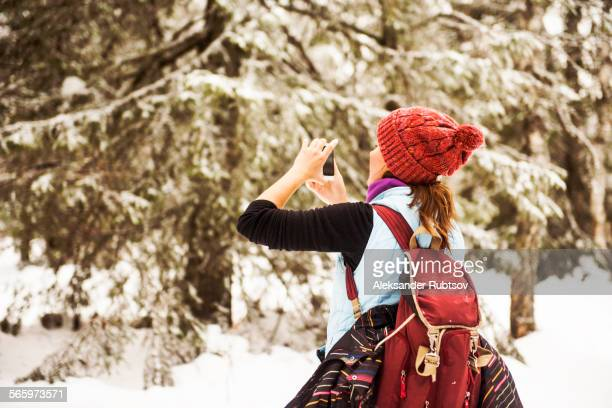 Caucasian woman photographing nature on snowy path