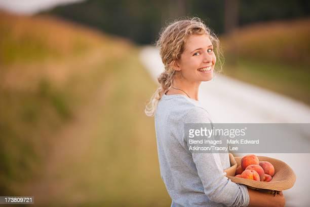 Caucasian woman picking fruit on rural road