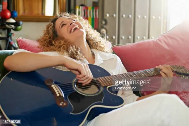 Caucasian woman playing guitar