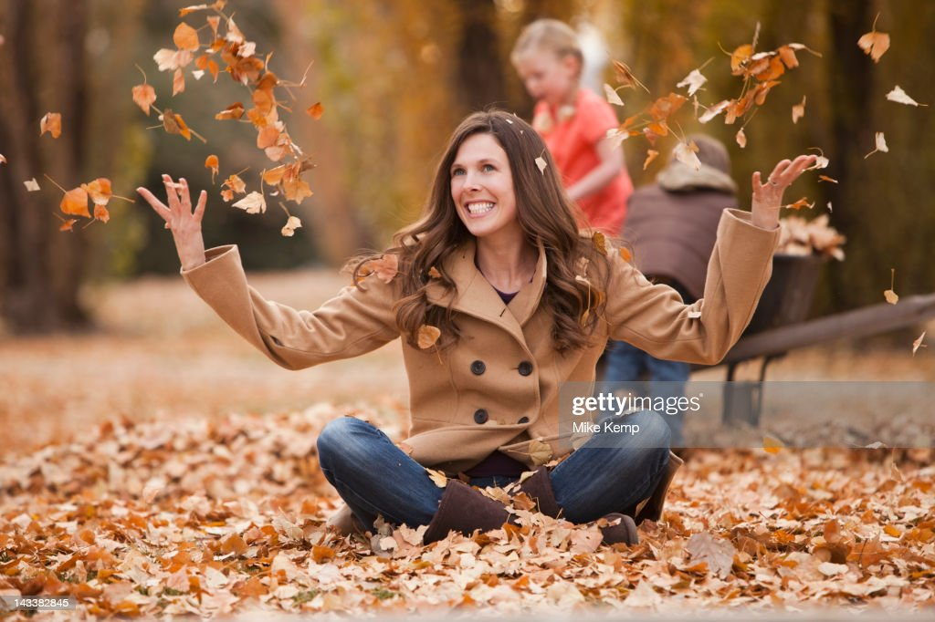 Caucasian woman playing in autumn leaves : Stock Photo