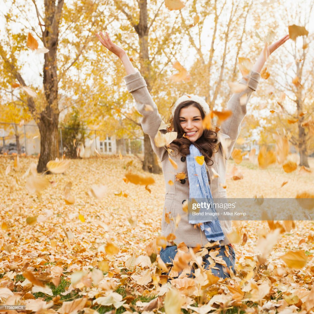 Caucasian woman playing in autumn leaves : Photo