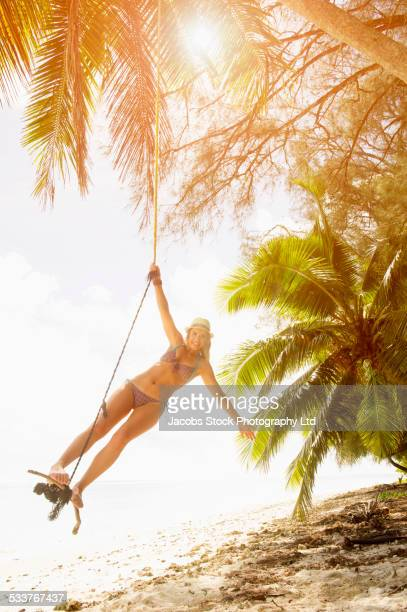 Caucasian woman playing on rope swing on tropical beach