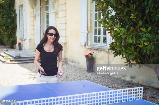 Caucasian woman playing table tennis in yard