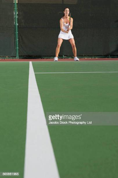 Caucasian woman playing tennis on court