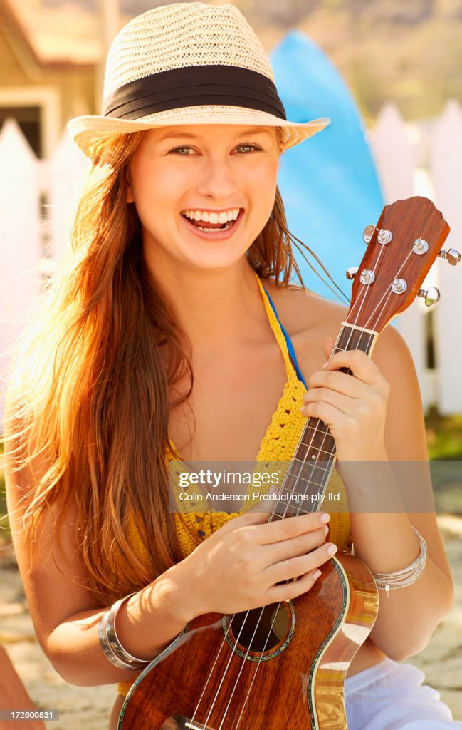 Caucasian woman playing ukulele on beach : Stock Photo