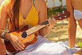 Caucasian woman playing ukulele on beach