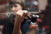 Caucasian woman playing violin overlaid with graphic design