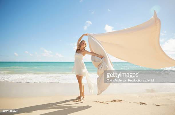 Caucasian woman playing with blanket on beach