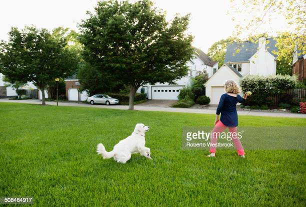 Caucasian woman playing with dog in park